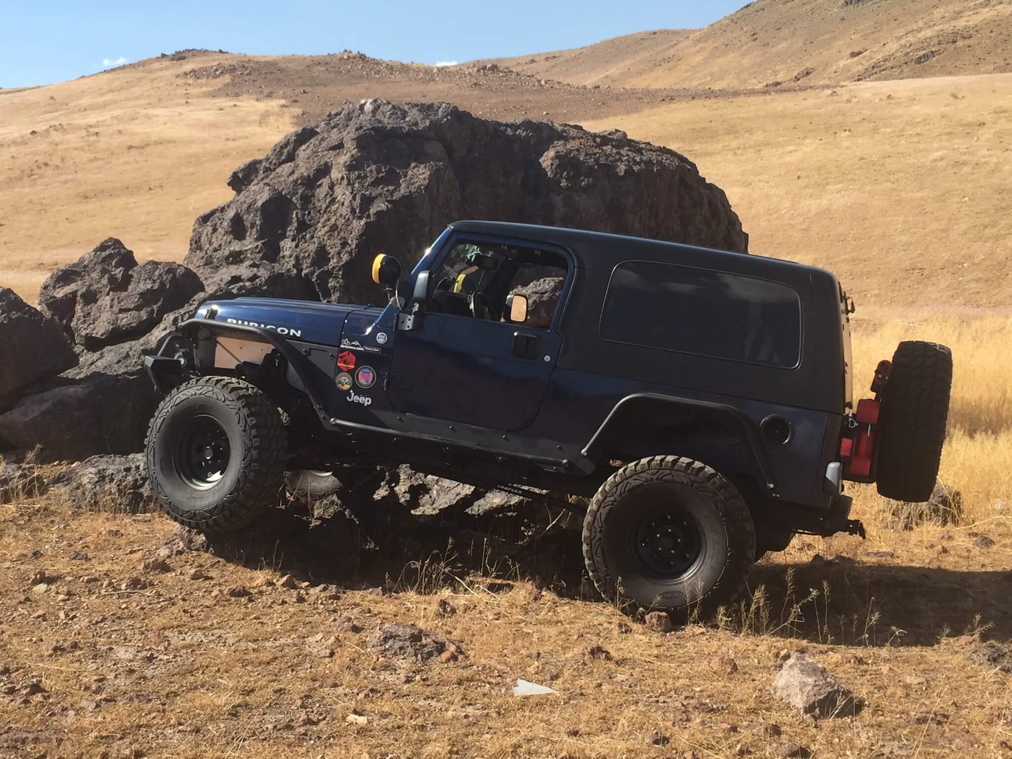 dark blue Jeep Wrangler driving through hills