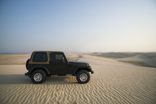 Jeep driving through sand